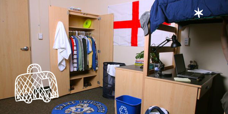 Dorm room with open closet, flag on the wall, and lofted bed