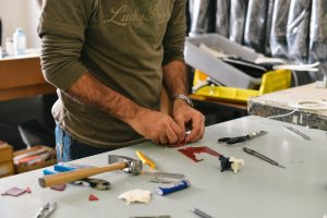 Man making an object at a workbench with a hammer, pliers, scissors, and craft supplies